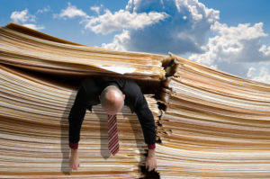 Business man caught under pile of files